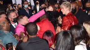 Conor McGregor napřahuje pěst ke zpěvákovi Machine Gun Kellymu, kterého se snaží odtáhnout Megan Fox.